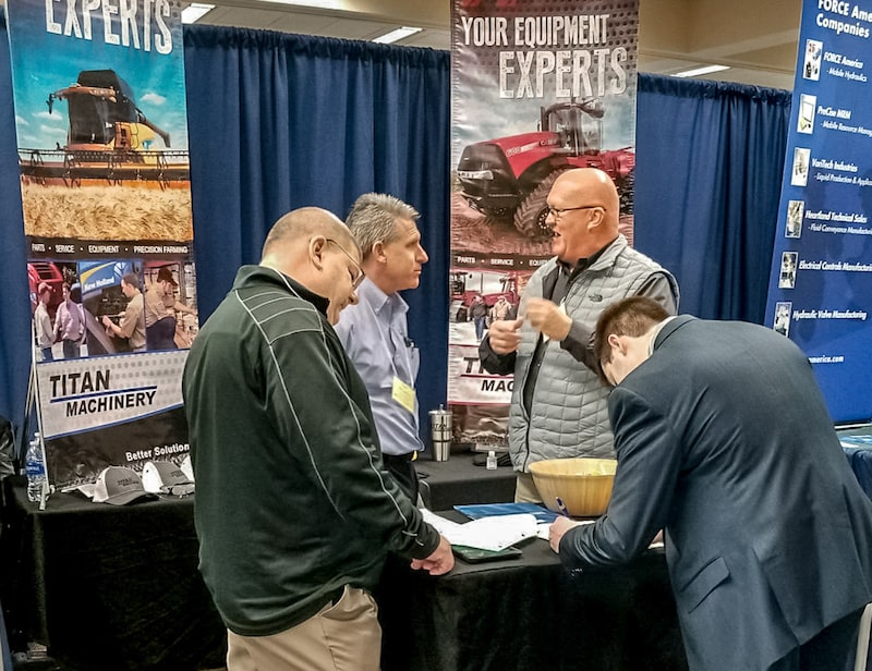 Titan employees at a career fair talking to students