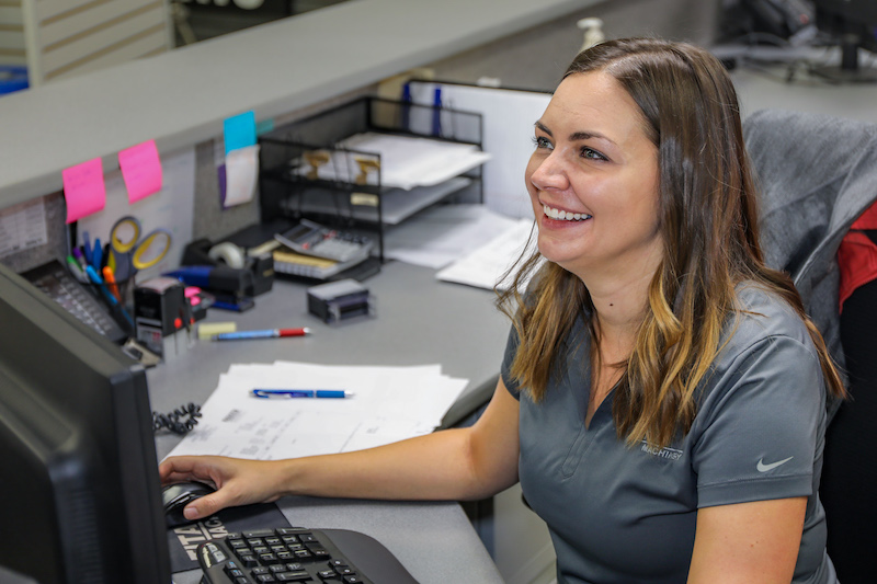 Smiling female at desk working on computer