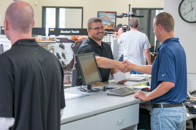 Titan Parts Sales Rep shaking hands with customer at parts counter