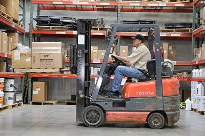 Parts Sales Rep operating forklift in warehouse