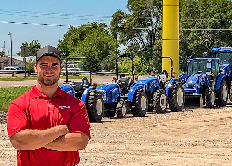 Business of Sales Intern in front of New Holland tractors