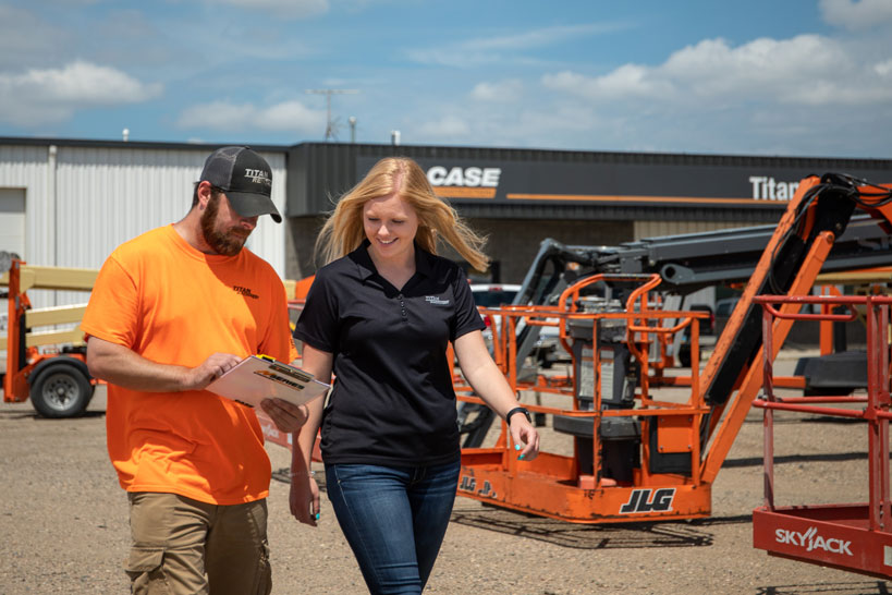 See female student learning from Titan employee at construction dealership