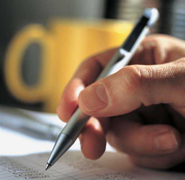 Hand holding pen signing document with yellow mug