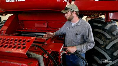 Titan Machinery service tech demonstrating maintenance on a Case IH 2388